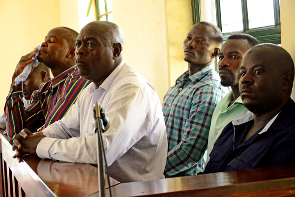 Muhammad Ssebuwufu (right) and others in the dock at High Court in Kampala