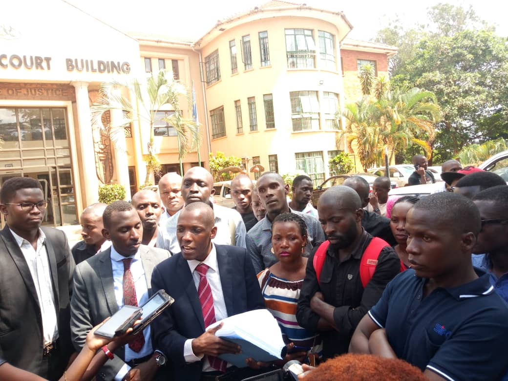 The group with their lawyer Mr Muwada Nkuuyingi after filing their case at Commercial Court. Photo by Rachel Agaba.