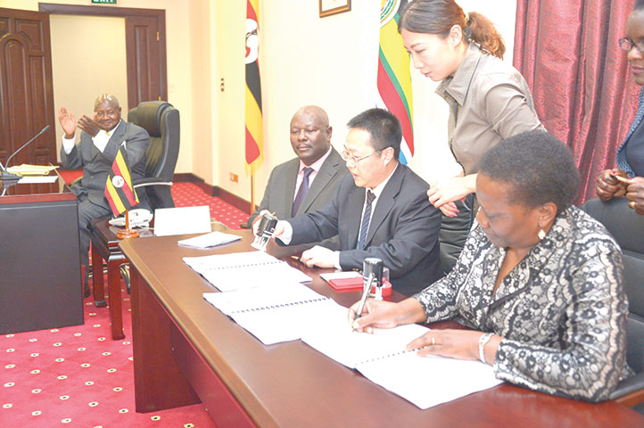 Chinese investors and Ugandan officials signing the deal over the Sukulu phosphate project as Museveni (L) cheers on