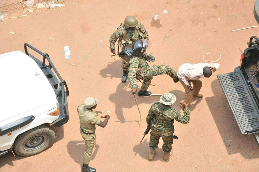 Security officers kick a citizen onto a truck (PHOTO/File)