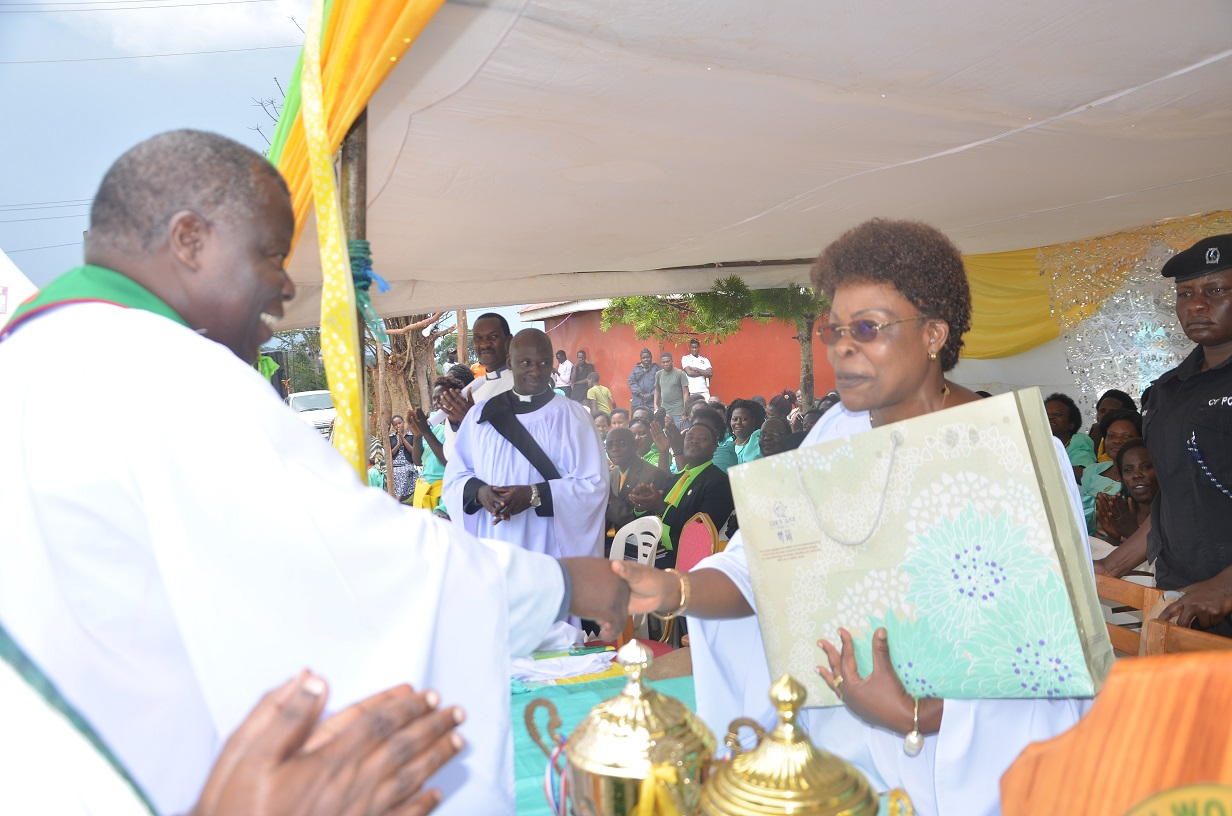 Ven. Canon Jonathan Kisawuzi the Archdeaconof Entebbe (L) hands a gift to Kampala Minister Ms Betty Kamya during the celebrations. Photo by Paul Adude