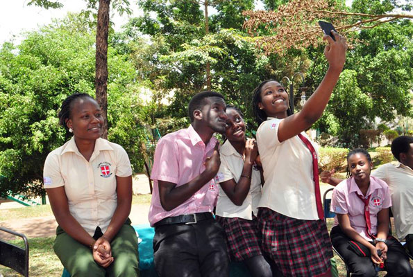 Students of Vienna College Namugongo take a selfie at school using a mobile phone. There has been a raging debate on whether it is right for students to carry mobile phones to school.  (PHOTO/Courtsy)