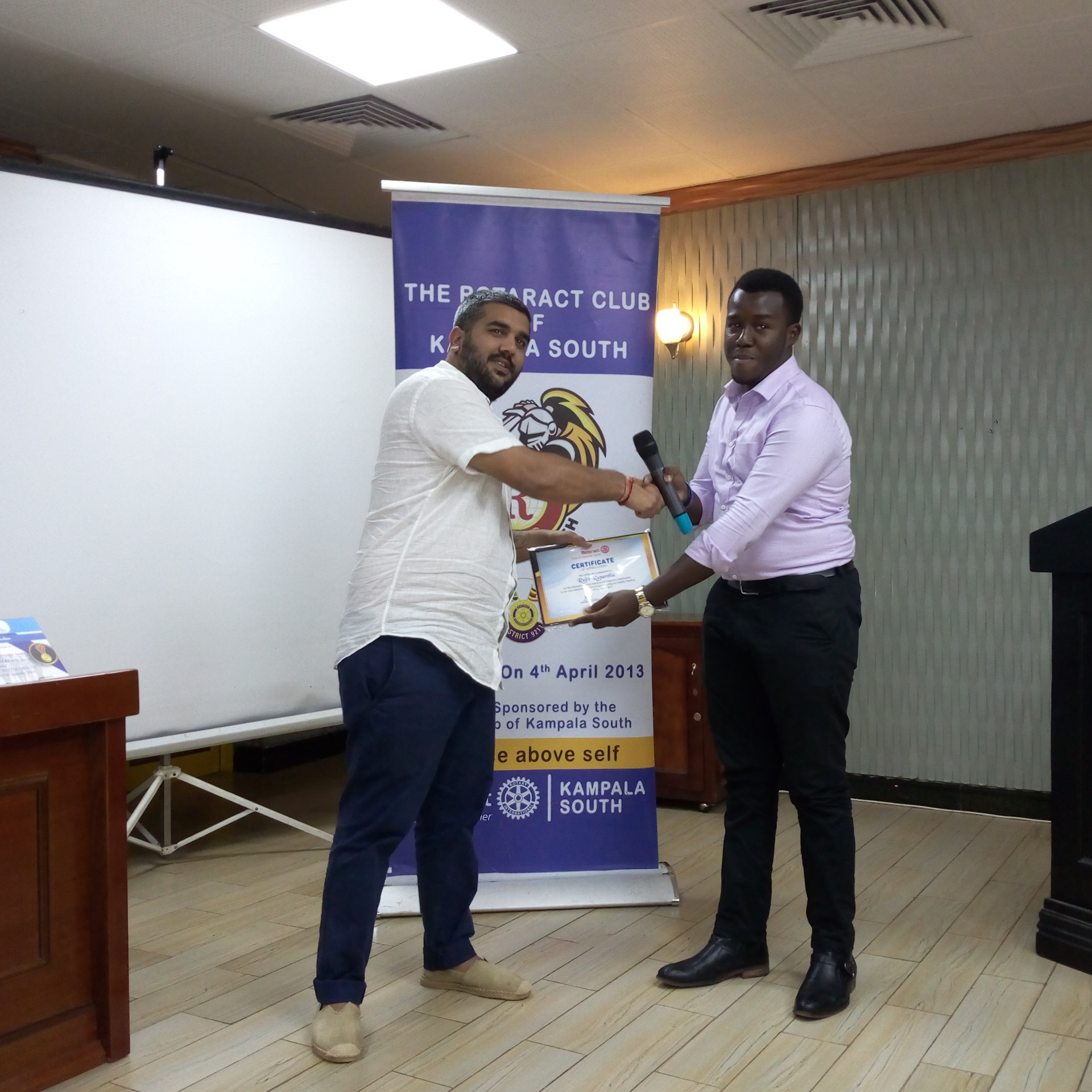 Mr.Rajiv Ruparelia, the Managing director Ruparelia group receiving a certificate of Appreciation after sharing business talk with the  the members of the Rotaract Club of Kampala South  at Hotel Africana (PHOTO/Abraham Mutalyebwa)