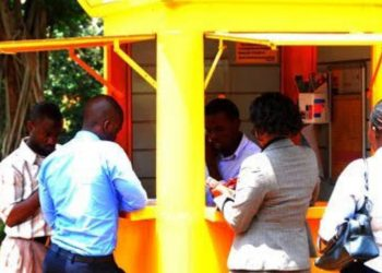 Mobile Money users que up at an agent for the service (PHOTO/File)