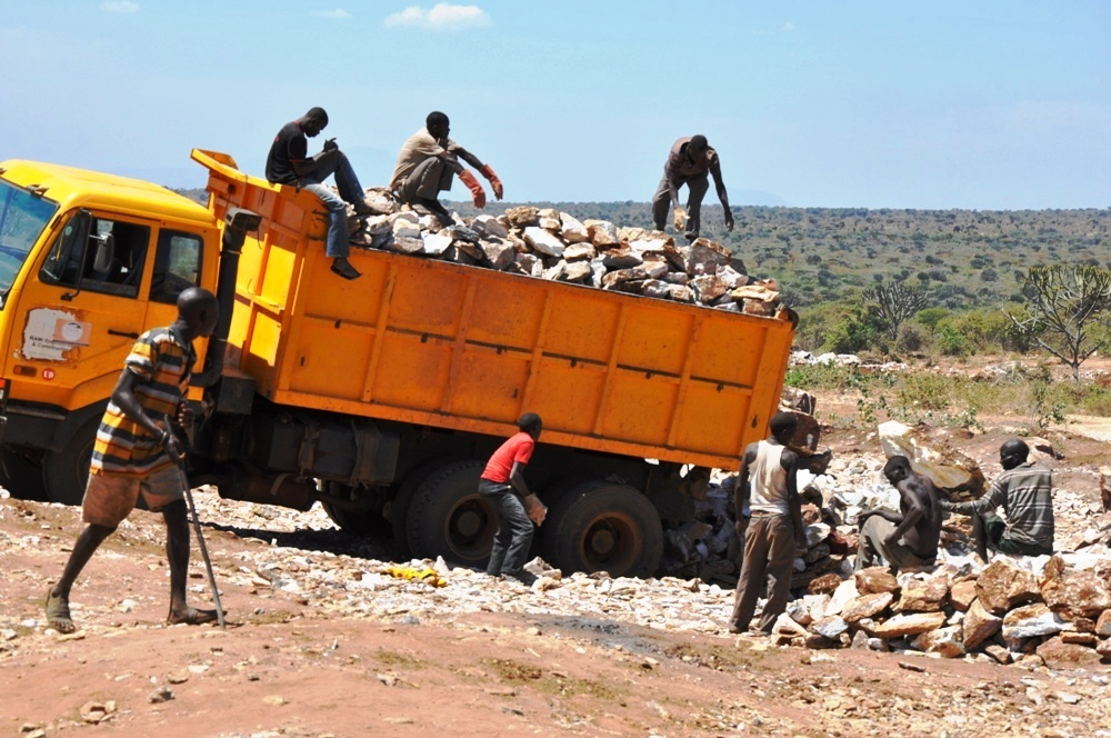 Karimojong men load marble stones to a truck that takes it to process in Tororo cement factory in eastern Uganda (photo by Jonathan Opolot