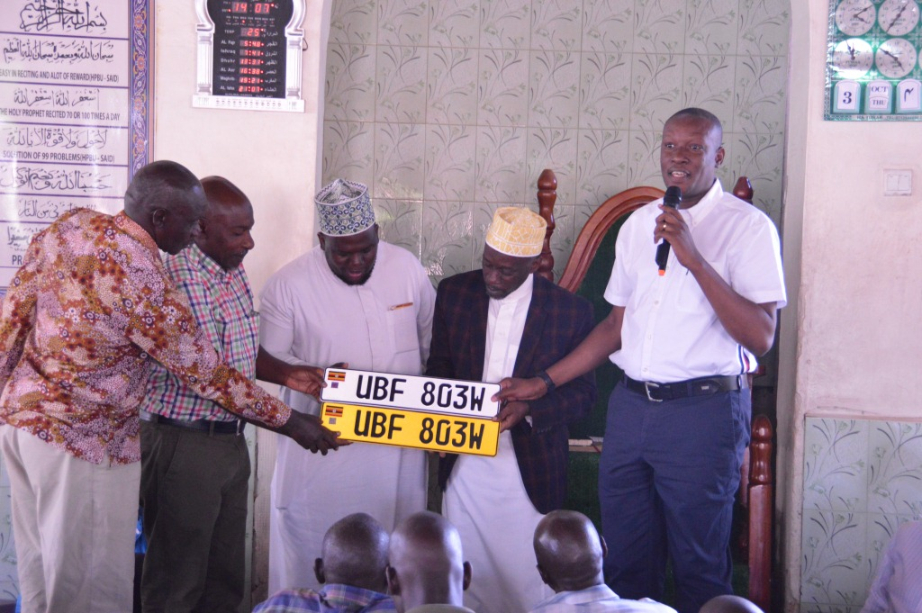 MP Michael Tusiime (L) handing over the number plates and the log books to Muslim leaders on Thursday (1)