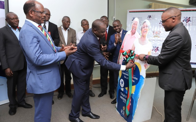 The Vice Chairperson of Council, Rt. Hon. Daniel Fred Kidega cuts the tape to signify the official launch of the MURBS Annuity Arrangement with ICEA Life Company as the Vice Chancellor, Prof. Barnabas Nawangwe and other officials applaud on 11th October 2019, Makerere University, Kampala Uganda
