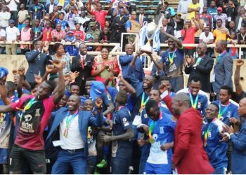 Bulemezi players and officials are handed the Masaza Cup by His Majesty the Kabaka of Buganda, Ronald Muwenda Mutebi II on Saturday. (PHOTO/courtesy)