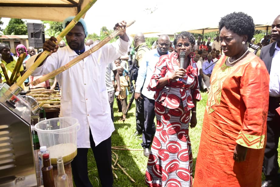 The Speaker of Parliament, Rebecca Kadaga, is shown how a sugarcane juice extractor squeezes juice out of sugarcane.