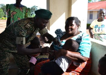 A UPDF officer vaccinating a child against