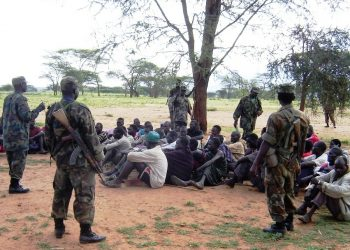 UPDF soldirs guarding Karimojong boys waiting to be screened after they were rounded up during cordon and serch in Nakapiripirit district in 2009 (photo by Jonathan Opolot)
