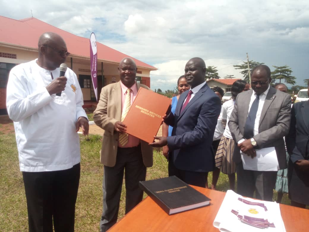 Justice Wangutusi David hands over SCP Registers to Sironko Court. (PHOTO/Courtesy)