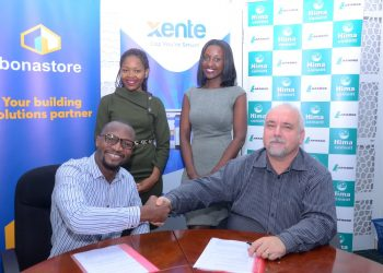 Francis Nkurunungi, Xente's Chief Operations Officer (Seated L) and Paul Bernard Kelly (Seated R), Hima Cement's Retail Manager shake hands after signing a Memorandum of Understanding to open an online shopping platform where Hima Cement and building solutions provider, bonastore Uganda will now avail their products to customers online. Looking on are Christine Kyokunda, Marketing Officer at Hima Cement and Lyn Tukei, Chief Marketing and Communications Officer, Xente