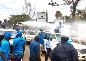 Police spraying very high-pressure water at FDC former president Kizza Besigye on Monday (PHOTO/File).