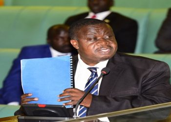 Minister of Justice and Constitutional Affairs, gen. Kahinda Otafiire, presents documents proving ownership of Njeru Stock farm during plenary sitting on Thursday