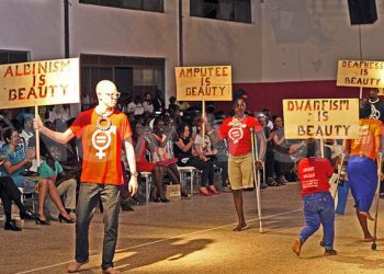 Models walk with placards detailing the differences in abilities that society looks at as disability