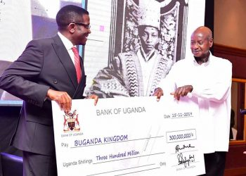 President Museveni (R) handing over a dammy cheque to Buganda Kingdom Prime Minister Peter Charles (PHOTO/PPU)