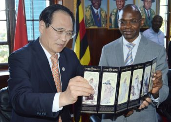 Honourable Fu Zhifang, President of the Shandong Provincial Committee of the CPPC (Left) presents a gift of the Shandong people to the DVCAA, Dr. Umar Kakumba (Right) during the visit on 11th November 2019, Council Room, Makerere University, Kampala Uganda (PHOTO/PML Daily).