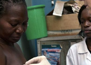 A breast cancer, is being prepared for a needle biopsy by a physician visiting from the United States, Dr. Constance Lehman, at Mulago Hospital in Kampala, Uganda