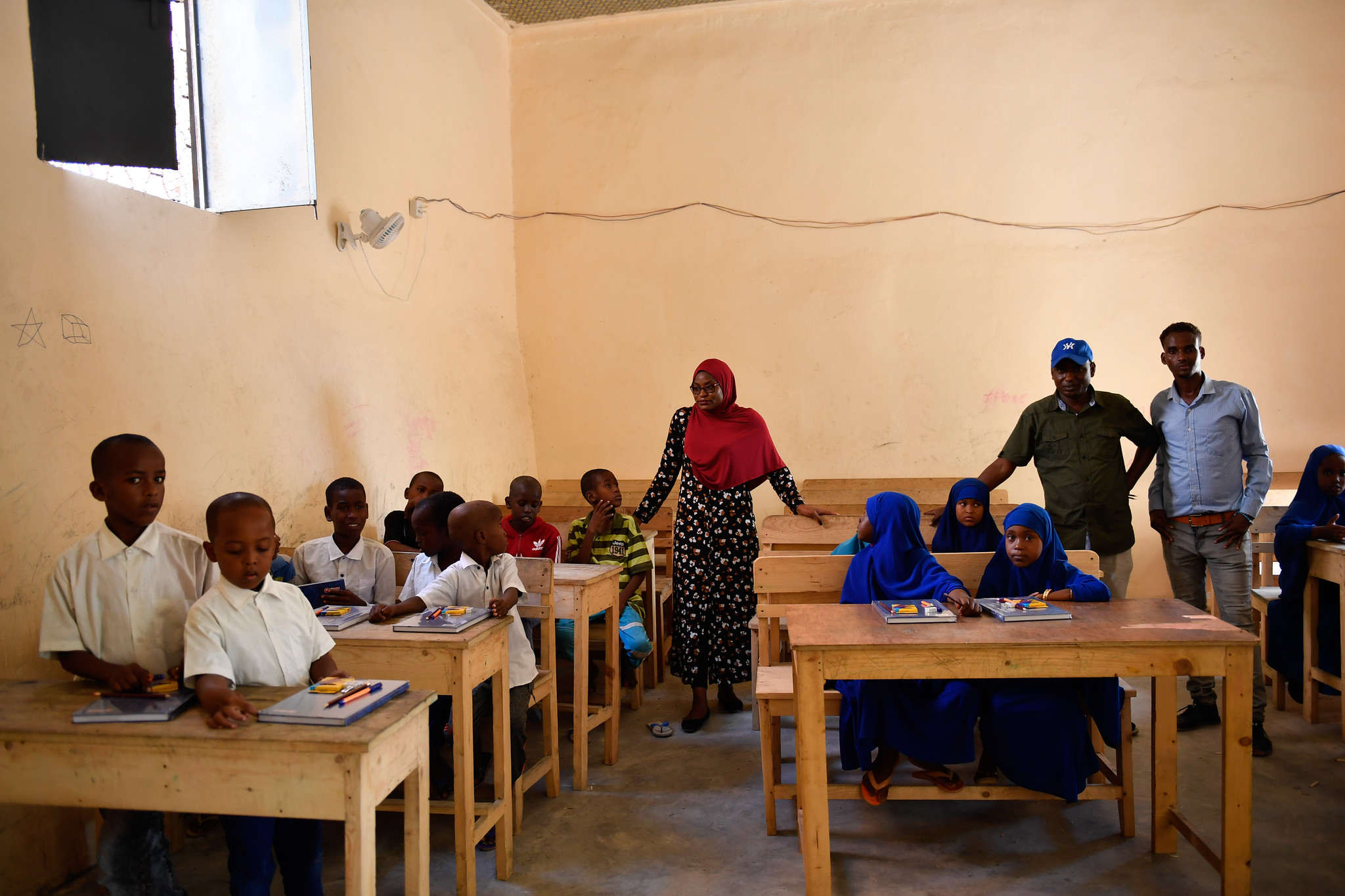 Ulrike Kahbila Mbuton, the AMISOM Human Rights Officer, stands amongst pupils at Qamar Primary School, after the AMISOM team donated an assortment of stationery to the school in Mogadishu on 19 December 2019. The school was renovated by AMISOM following several terrorist attacks in Mogadishu that destroyed it, leading to its closure in 2016. AMISOM Photo / Omar Abdisalan