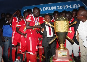 Acholi players prepare to receive the FUFA Drum trophy from FUFA Vice President Justus Mugisha on Tuesday. (PHOTO/FUFA)