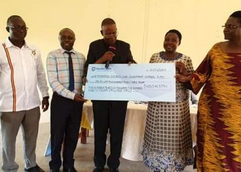 Minister of Tourism, Ephraim Kamuntu (2nd R) and UWA's Sam Mwandha (C) handing a dummy cheque to district officials (_PHOTO/Courtesy)