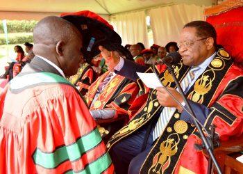 The Chancellor-Prof. Ezra Suruma (Right) confers a PhD upon a male Graduand (Left) during Day 2 of the 69th Graduation Ceremony on 16th January 2019, Freedom Square, Makerere University, Kampala Uganda. (PHOTO/File)