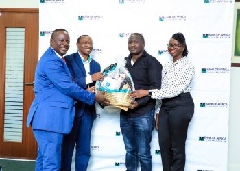 Executive Director bank of Africa  – Bernard R. Magulu and Managing Director Arthur Isiko award one of the active mobile wallet customers. Far right is the Head Retail Banking Stella X. Atim Engena (PHOTO/PML Daily)