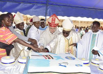 President Museveni with Bishop Paul Ssemogerere (2nd right) and Minister Chrysostom Muyingo (right) and the Apostolic Nuncio Archbishop Luigi Bianco (2nd left) cut the cake during Saturday's celebrations. (PHOTO/ PPU)