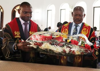 The Vice Chancellor-Prof. Barnabas Nawangwe (Right) and Deputy Vice Chancellor (Academic Affairs)-Dr. Umar Kakumba (Left) lay a wreath on Prof. Johnson Acon's casket during the Funeral Service (PHOTO/Courtesy).