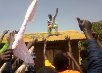 State Minister for ICT Peter Ogwang is hoisted up on the roof by his youthful voters as he launched new NRM office in Getom Subcounty. Ogwang is in Katakwi for the first time since his ministerial appointment (PHOTO/Ocaido)
