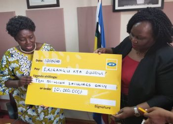 Speaker Kadaga receives a dummy cheque from MTN Uganda's General Manager Cooperate Affairs Enid Edrom (PHOTO/Courtesy).