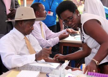 Dr. Diana Atwine the Permanent Secretary,  Ministry of Health takes blood samples from President Museveni who publicly tested for HIV in 2013. The President has led from the front as the country revived the health sector that is key to service delivery. (PHOTO/File)