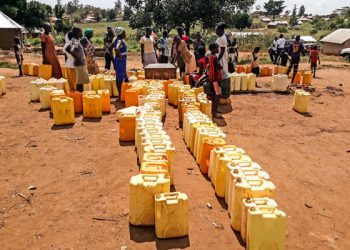 Refugees at the Kiryandongo settlement line up their jerricans at a borehole in the camp