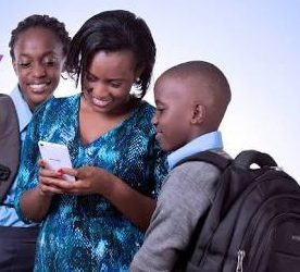 Mum helps children to check UACE results on phone (PHOTO/File)