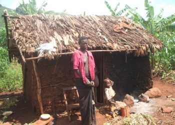 Ms Wakooli stands next to her house which serves as a kitchen, store house, bedroom for about seven people in Kiwata village, Bugobero sub-county in Manafwa district. David Mafabi