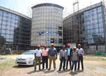 The delegation infront of the mega PAU and DOP offices currently under construction