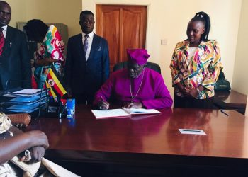 Bishop James William Ssebaggala flanked by Head Mistress and Director Muzza High School signing in the visitors' book (Elizabeth Namajja).