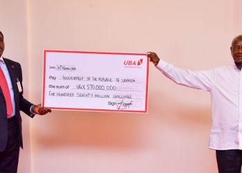 Mr. Johnson Agoreyo CEO UBA handing over a dummy cheque to President Museveni at State House Entebbe (PHOTO/PPU)