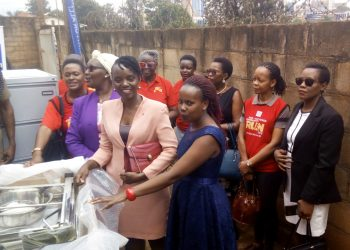 President of Rotary Club of Kisugu-Victoria view, Rtn. Goretti Masadde, joins parents and staff of British School of Kampala (BSK) handing over the items. (Photo by Amon Kizza)