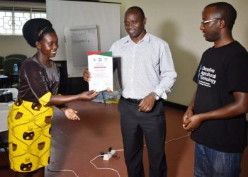 Prof. Archileo Kaaya (C) passes on the certificate to the trainee representing the Agricultural Officer Tororo (PHOTO/PML Daily)