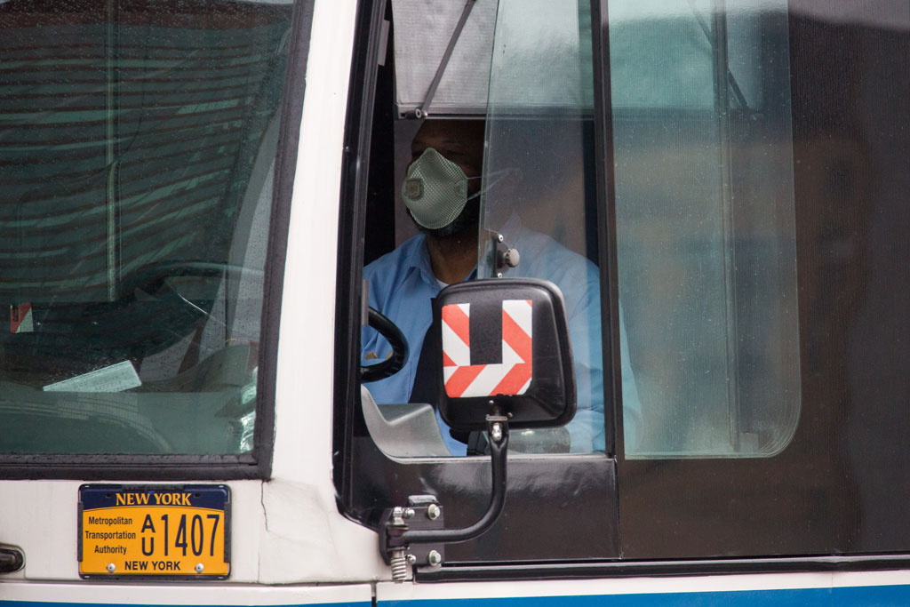 A bus driver wearing a face mask steers in the Brooklyn borough of New York, the United States, on April 3, 2020. (Photo by Michael Nagle/Xinhua)