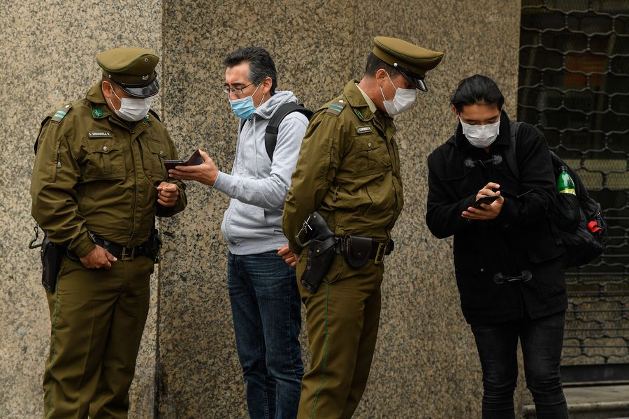 """Police check people's paperwork in Santiago, Chile, March 27, 2020. Chile has adopted a """"progressive quarantine"""" to help control the spread of the disease in the country. (Photo by Jorge Villegas/Xinhua)"""
