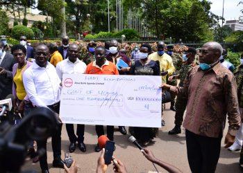 Mr. Hamis Kigundu hands over UGX. 100M to Prime Minister Ruhakana Rugunda (PHOTO/Courtesy)