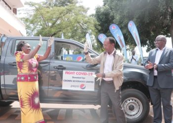 (L- R) Minister Mary Karoro Okurut and Dr. Amos Nzeyi share a high-five after receiving a brand new pick-up double cabin as Mr. Robert Kwesiga, the secretary General Uganda Red Cross smiles (PHOTO/Courtesy).