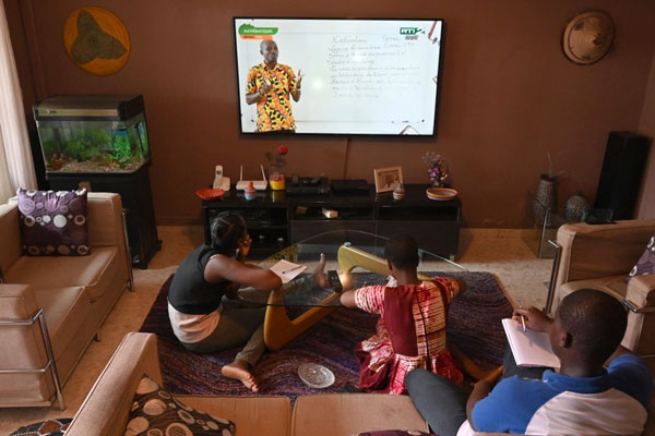 Children take school lessons on television at their home in Abidjan on April 10 following the outbreak of Covid-19 (PHOTO/Courtesy).