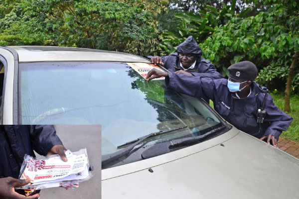 Traffic police officers removed fake stickers from vehicles during an operation in Kampala