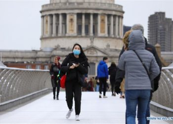 A person wearing a mask walks across the Millennium Bridge in London, Britain, on March 9, 2020. (Photo by Tim Ireland/Xinhua)