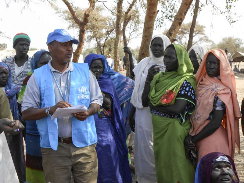 UNHCR staff member discusses a soap distribution with refugee women (PHOTO/Courtesy).