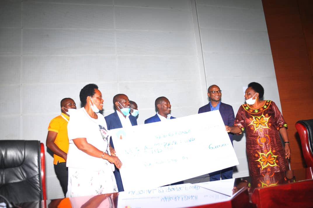 Mrs Schola Ndyagambaki, hands over AMDA cheque to Minister Karooro (PHOTO/R. Kabuubi).